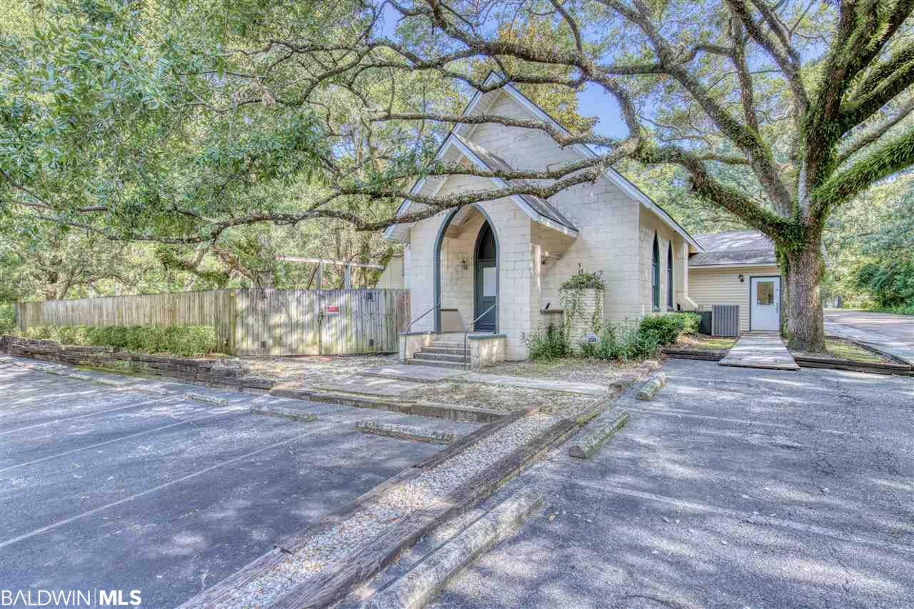This property is zoned R-2 and sits among the beautiful oak tree lined streets of Old Town Daphne. Your chance to own almost a half acre, on a corner lot, within walking distance to May Day Park and Main Street. Originally the front portion of the building was a place of worship and the back section was a residential property. The front portion is of masonry construction and rests on a pier foundation. The windows are of the gothic or cathedral-style design. Interior finish consists of vinyl tile flooring, painted gypboard, plaster walls, and suspended acoustical ceiling tile. The rear building or former residence is of concrete block construction and rests on concrete slab foundation. The building was converted into a daycare school in the