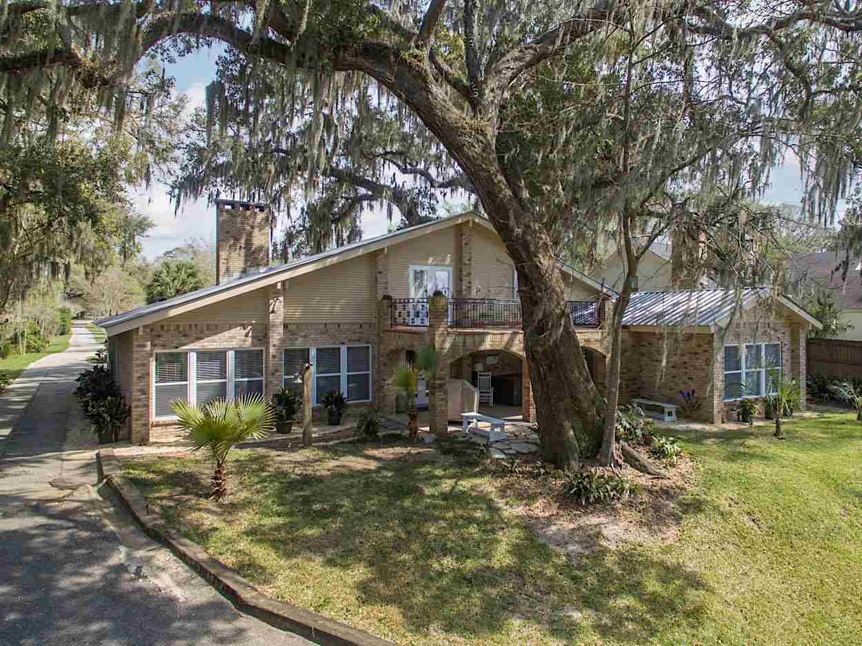 Huge Price Improvement! Now just $1.4 M.Your beach front Paradise awaits. Custom rebuilt home with views of Mobile Bay from your living room, kitchen and master bedroom. Drive down your own driveway to the beach to Watch the sun set through 200 year old moss draped oaks that give way to a breathtaking view of your private beach over looking a stocked pond, Private pier and Gazebo.  No worries about flooding since this home was built 800 ft from the Bay up on a hill.  Home was completely gutted & rebuilt in 2007 with Custom cooks kitchen with 5 burner gas stove, granite counters, wine fridge etc. Wood burning Fireplace was hand built using hand cut stones.  Juniper lined walls in the great room with custom built ins.  Your master retreat has views of the Bay from a wall of windows and access to an outside covered patio with hot tub and TV.  Juniper lined master closet with built in drawers for added storage. Bath has a jetted tub, tiled shower, dual sinks, makeup counter & a separate water closet.   Hardwood floors throughout the master with beadboard ceilings. Large laundry room with large pantry and room for a freezer with split brick floors flowing out to the kitchen.  Media room/bedroom with full bath and queen size built in bed.  Plenty of outdoor living space for entertaining and watching the sun set over the Bay.   Property also has an adorable, one bedroom cottage fully contained with a full bath, walk in closet, kitchen and living area with full size washer and dryer, vaulted tongue and groove ceilings with exposed beams.  It could be a guest suite or a mother-in-law cottage or with income producing potential.  Large 30 x 70 outbuilding with 5 large roll-up bays.  Separate juniper lined office, unfinished bathroom, work shop and cedar lined walk-in closet. Perfect Man cave to store all the toys and tools.  This property has too much to list and is one a kind.  Character abounds throughout this property.  It is a must see and once you see it you will be home.