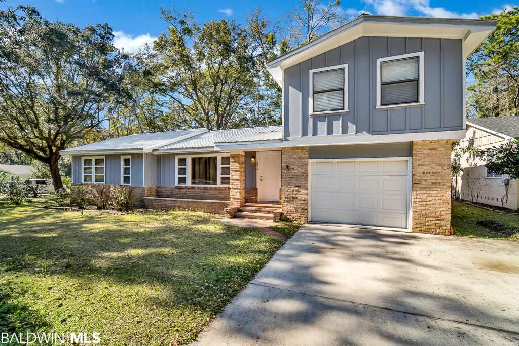 MOTIVATED SELLER SAYS BRING AN OFFER! Located at the intersection of two of the best streets in Fairhope sits 372 Liberty Street! This home is full of original 1950's charm and tons of possibilities for today's buyer! The exterior of the home is accentuated by large trees and mature landscaping, a neutral brick and wood siding, and a metal roof. Walking in the front door you'll see original hardwood floors and fireplace with brick surround, and a charming kitchen with a built in table and bench seating. On the main level are the living area, kitchen, master bedroom, second bedroom, and a full bath. Upstairs are two more good sized bedrooms and a full bathroom. Recent upgrades to this home include AC Replacement (2015), New gas water heater (2019), new metal roof (2016), New gas range (2019), Dishwasher (2016), Refrigerator (2019). With some updating this home would truly be a standout!