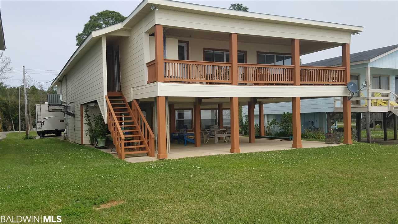 DRASTIC PRICE REDUCTION! REDUCED OVER $100,000. Sunsets call you to this well maintained and loved home on Mobile Bay. This property offers a bit of everything: breathless views, a pier and boathouse, new additions, work shops, RV parking with hookups and outside living space. There are two bedrooms and two bathrooms upstairs, and a separate bed and bathroom at ground level. The home has fresh exterior paint.  Located close enough to downtown Fairhope that the water view drive to town is like a up-close personal scene from one of the many movies filmed in this area. The beaches of the Gulf coast are a easy 45 minute trip. Come see why Fairhope is ranked as one of the best places to live in America. This home is priced to sell and it is hard to imagine that you can have a water front lifestyle at this price. There is plenty of opportunity to make your personal mark on this property.