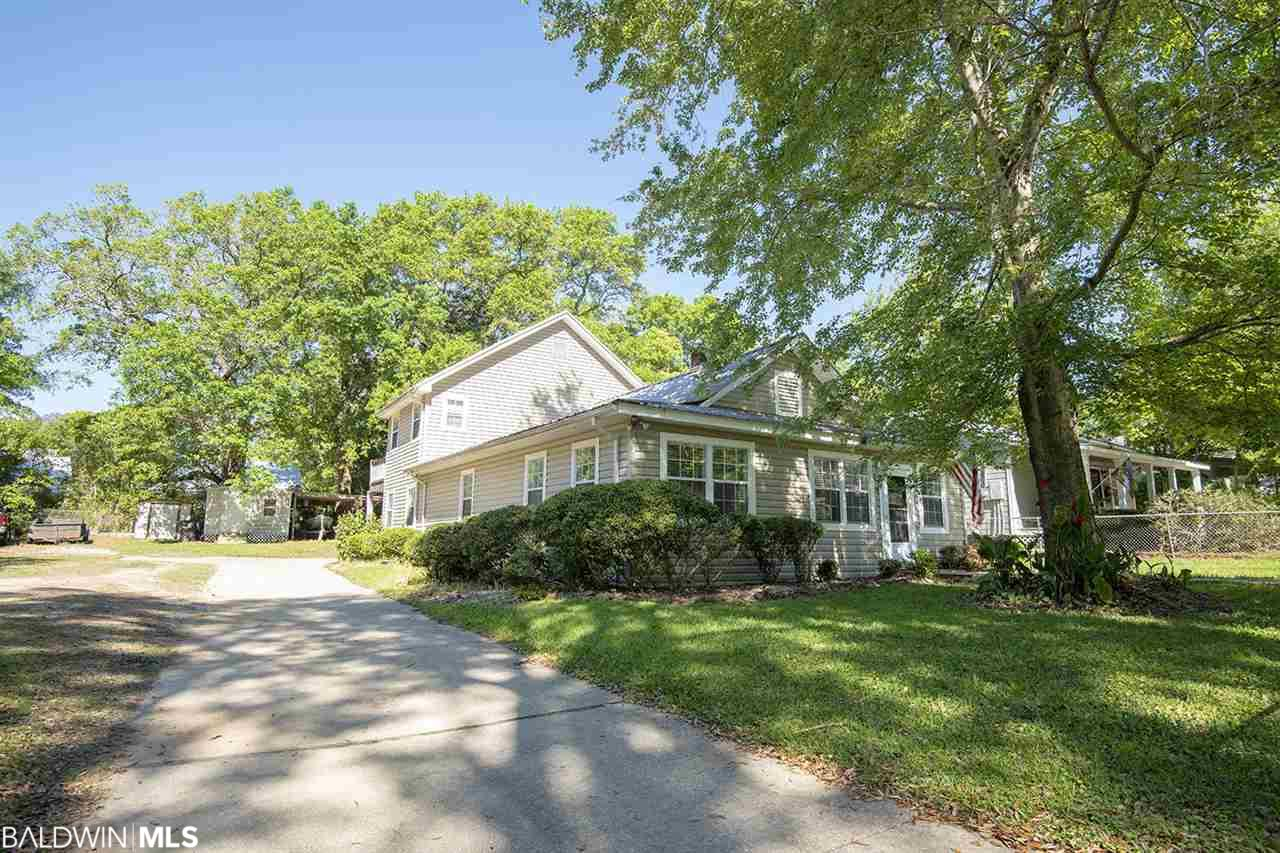 Location! Location! Location! Walk to downtown Fairhope from this charming cottage that sits on a 100' lot or clear the house and build two custom homes on the two 50' deeded lots. The Upstairs master suite opens to huge wooden deck to sit and enjoy your morning coffee. Beautiful custom cabinets in the kitchen. A Comfortable den with wood burning fireplace to enjoy those cool winter nights. The Large back room could be used for rec room, guest room or formal dining area. HVAC replaced March 2019. Metal roof Inspected April 2019. This home even comes with a built in safe! Bring your imagination and turn this into your dream home!
