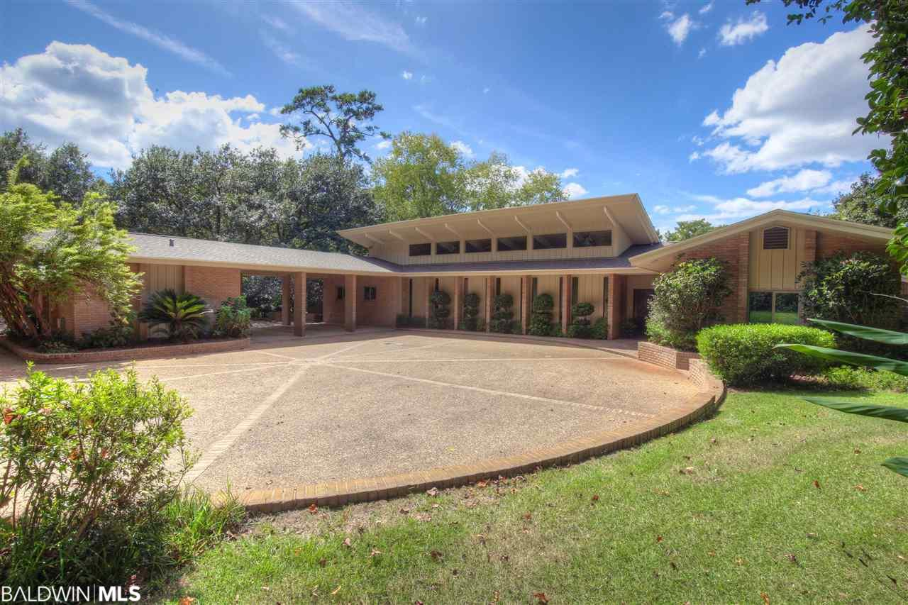 This bayfront home is a masterpiece built with impeccable charm and detail.   The estate lot features over 160 front feet on Mobile Bay with an incredibly wide sandy beach.  From all rooms of this home, the bay shines through.  Oversized great room, formal dining room with whitewash vaulted ceiling and separated by a see-through wood burning fireplace and built in cabinetry.  Bedrooms are split.   Oversized master with an enormous walk-in closet.  Fourth bedroom is staged as an office but can easily convert to a bedroom.  Guest suite is located off of carport and has built in stove, refrigerator and separate bath.  Relax and soak up the luxurious pool, barbeque for a large crowd and enjoy your sunset on the bay.  Easy commute to Mobile and downtown Daphne.