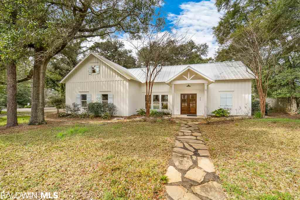 Southern perfection in Fairhope's Fruit & Nut District!  This beautiful home was remodeled in 2018. Situated on a spacious corner lot, this home has an open, split plan with 2 master suites downstairs and tons of storage! Walk into a beautiful cathedral ceiling foyer into a bright kitchen with gorgeous cabinetry, quartz countertops, stunning fixtures, fabulous wide plank Hickory wood flooring and lots of natural light. The patterned tile in the utility room is a classic touch and it works beautifully with the modern railing on the stairway.  Upstairs offers two more large bedrooms and a huge bathroom.  There's also a smaller room currently used as a Library that connects to a long hallway that is perfect for a small study or homework area. This home also has an attached side entry 2-car garage with automatic opener which is icing on the cake for this area!! If all that wasn't enough, the property boasts several large oak trees, including a tree swing on the front corner.