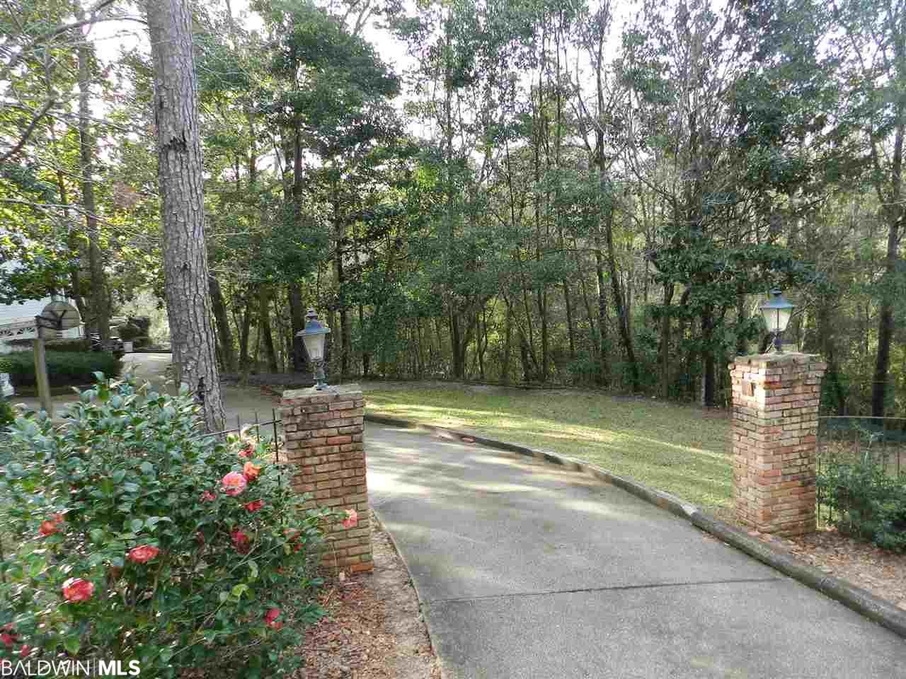 Waterfront residential lot on Rock Creek just steps from Mobile Bay. Exclusive Sans Souci subdivision with deeded access to Beach and Pier with Gazebo on Mobile Bay. Enjoy private waterfront with HOA maintained boardwalk/riverwalk and neighborhood foot paths. Also fronts scenic Hwy 98 in Old Montrose adjacent to Ecor Rouge (highest point on US coast between Mexico and Maine). The entrance to lot has an existing paved driveway with brick columns and wrought iron fence.