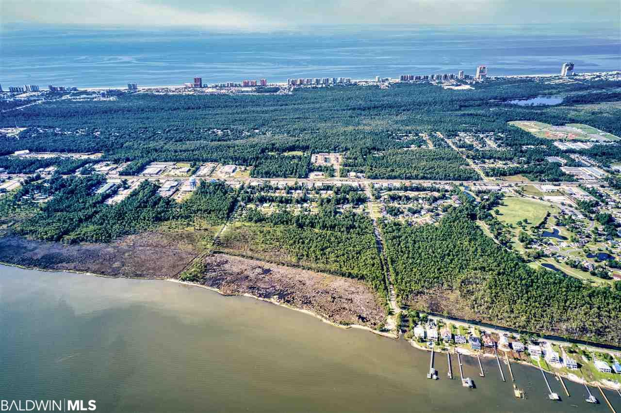 "This is a 23.6 acre (+/-) tract of land located directly on Wolf Bay inside the Orange Beach, AL city limits.  The tract consists of three contiguous properties: PPIN #227048, 102816, 102786.  The Northern border has a sandy 712"" coastline with a direct water view.  The rest of the property fronts a paved city street with lighting and sidewalks and has beautiful mature trees with lots of shade, plus a scenic one acre fresh water pond in the lower section.  Property has easy access to the Baldwin Beach Express to the interstate.  It is currently zoned RS-1, Single Family Residential, with no restrictions, but more intensive uses are permissible based on approval.    Orange Beach is a community with a growing population, quality educational institutions and in-land waterways with access to the Gulf of Mexico.  Measurements, amounts and information was obtained from Baldwin County records and is deemed credible, buyers should verify information important to them."