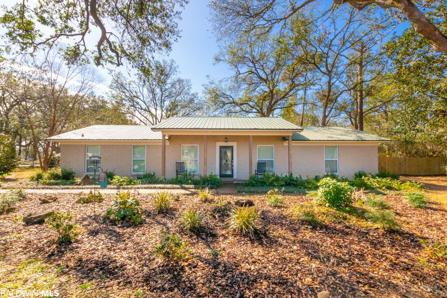Renovated ranch beauty in Fairhope now available! Originally constructed in 1975 and renovated in 2015, this gorgeous 3 bedroom, 2 bath home is move-in-ready and includes so many wonderful features. Situated on just over 1 acre of of land on a corner lot, the property boasts a circle side drive, as well as a gated entrance with carport. Metal roof was installed in 2014 and HVAC was installed in 2020. Inside, you'll love the open concept floor plan with a separate dining room. The large wood burning fireplace is a focal point of the living area and is open to the kitchen. Granite countertops, shaker style cabinets, tiled backsplash, pro series kitchen appliances and split brick floors adorn this beautifully remodeled cooking space. The large utility room with half door is a must see and perfect for containing pets. The guest bath features a granite vanity and frameless shower door. The master bath also features a granite vanity and classic, white subway tile. Bedrooms, living, dining and hallway have laminate flooring. Outside, you'll fall in love with the space to entertain, large oaks and fenced in yard. Just beyond the fence, there is a 20x30 workshop with automatic door, perfect for storing tools and toys. This location can't be beat... minutes to downtown Fairhope, the bay and the beach! Schedule your showing today!