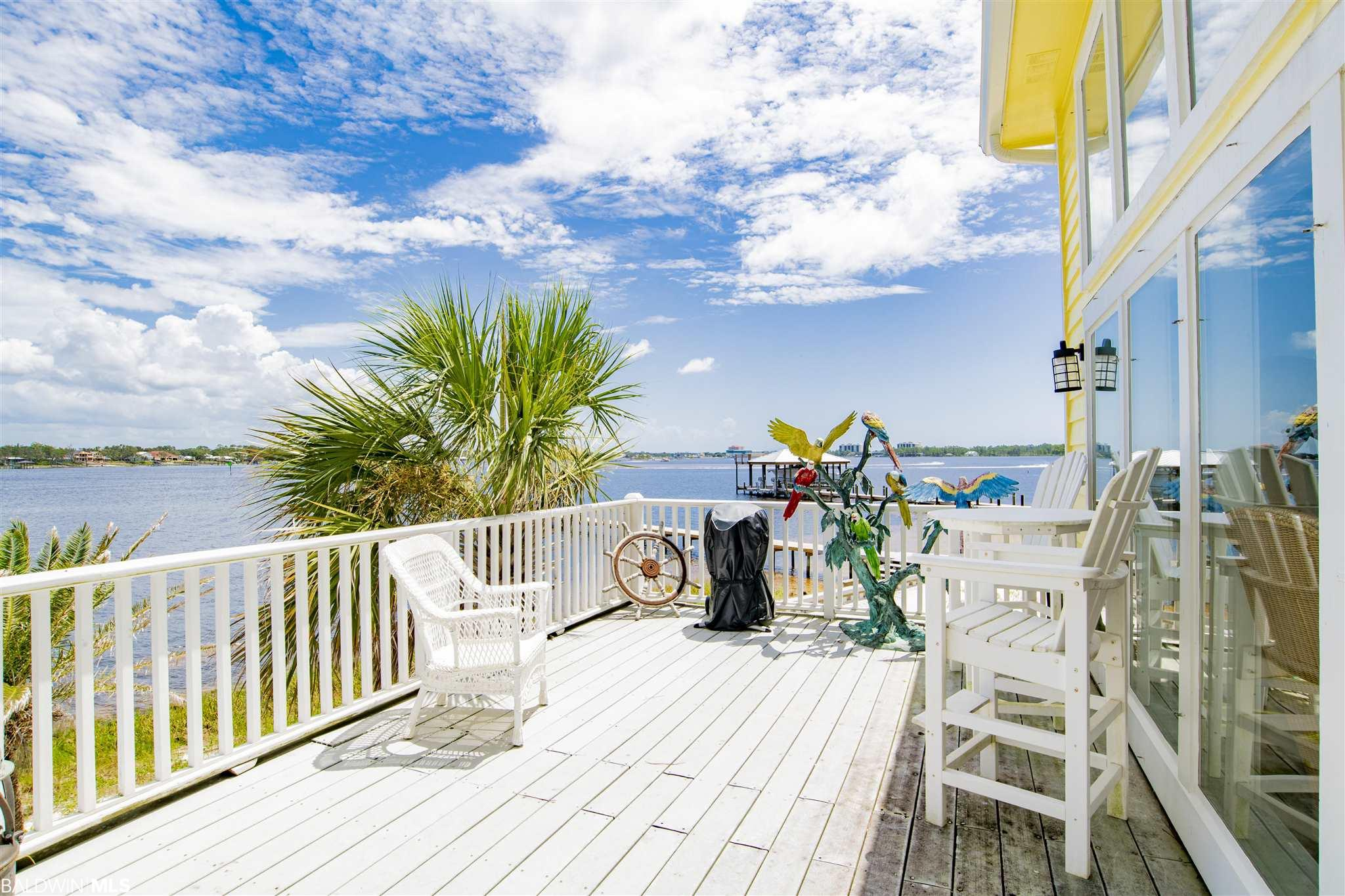 Most properties on Ono Island are locations; this property is a take-your-breath-away destination. It's such a lovely thing to experience the wide open panoramic views of Bayou St. John and the Intracoastal Waterway, magnificent sunrises and sunsets and white sandy beaches from this indoor/outdoor abundantly charming Caribbean/Key West style cottage on one lot and undeveloped sanctuary with the second lot. This enchanting destination's natural beauty offers a perfect 214' of waterfront refuge and deep water dockage. Owner has inspired an outdoor oasis surrounded by Heritage Live Oak trees, covered and open patios, large picture windows overlooking the bay and ICW, a private master with sunrise/sunset screened porch. Highly sought after destination on a quiet cul de sac offering a sense of freedom. Truly a magical and forever place.