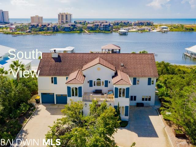 BOAT LOVERS DREAM HOME! Well-appointed 6 bed/5.2 bath home on an approx 1-acre lot, 22 ft above sea level (no flood insurance required) on prestigious Ono Island. The 40x40 covered dock with a 7,500 lb boat lift and additional deep water slip (10ft depth) to accommodate a large yacht. The dock includes an outdoor kitchen, open loft, fish cleaning station, fish lights & retractable hoses. Two levels of ultimate outdoor entertaining space (3000+ sq ft) with breathtaking views of Old River & the Gulf of Mexico. Located close to Ono bridge for easy access. This home has it ALL. The kitchen has a Thermador six-burner gas stove with griddle, Thermador warming drawer, Subzero refrigerator, wine cooler, Bosch dishwasher, Ice-Matic cone ice maker, wet bar & additional freezer in butler's pantry. Off the kitchen is a north-facing balcony right above the exterior foyer. Dual en suites master bedrooms with the primary master suite having his/her bathrooms, fireplace with gas & wood burning logs with remote, jetted tub & additional seating area. Both masters have balcony access & beautiful river views. Right off great room step onto your 1500 sq ft balcony with an outdoor kitchen featuring granite countertop stainless gas grill, stainless true refrigerator, big green egg, and outdoor speakers. Take the spiral staircase to the third deck with a panoramic view or take the staircase downstairs to your 1500 square foot covered porch with swinging bed, sauna & outdoor shower. The yard is a gardener's dream with raised beds, grapevines, fruit trees including apple, pear, pomegranate, fig, & enough citrus trees to line the driveway. Upstairs downstairs laundry room and kitchen. Work out in your large gym than play volleyball on your private beach. One of the few waterfront homes in the area with NO DAMAGE from Sally. The home has hurricane shutters & was sealed with Sherwin Williams, Last-O-Coat 3 years ago with a 10-year warranty. Hurricane roof with up to 150-mile winds.
