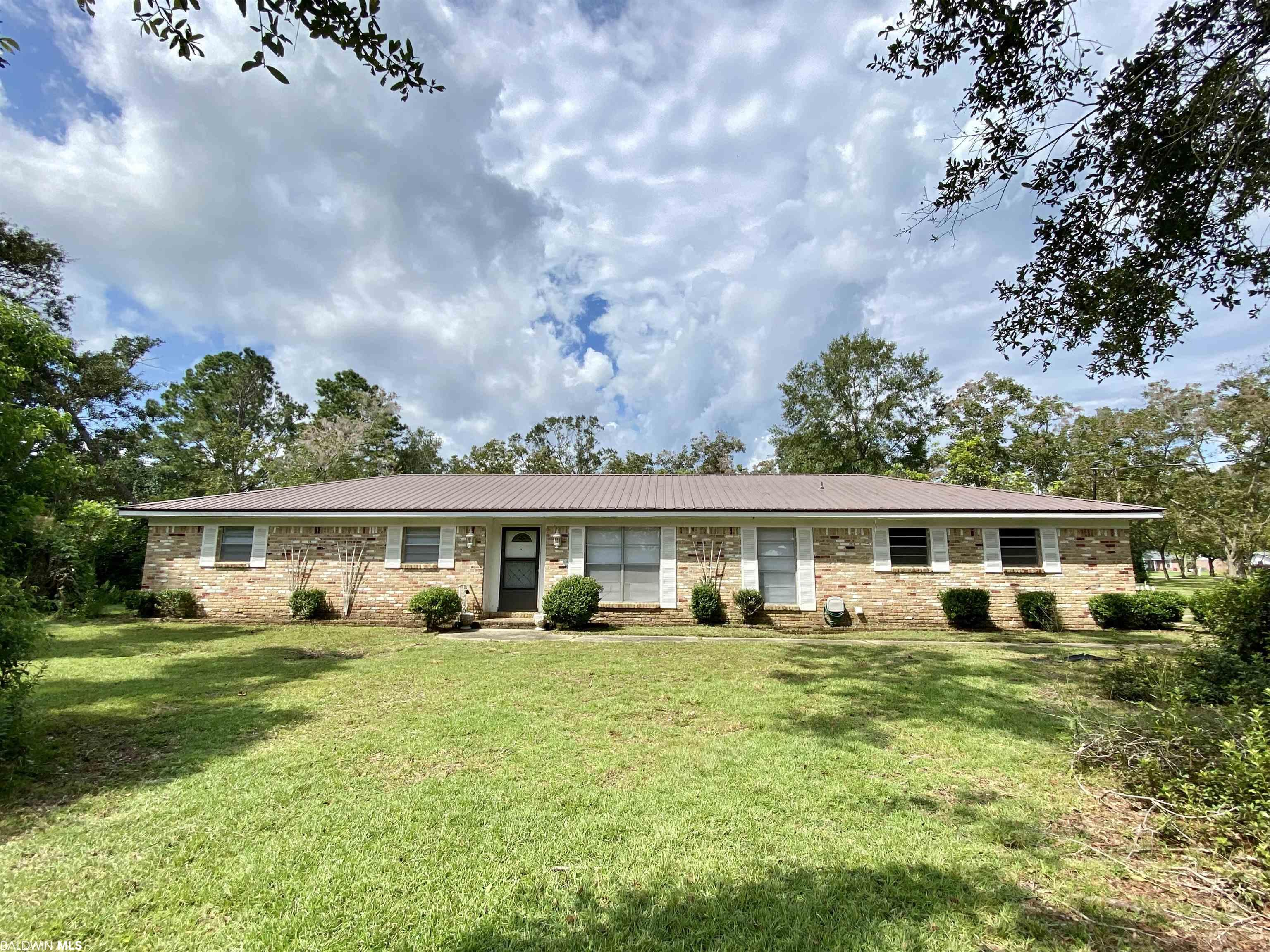 A home with a history and new opportunities! The original owner was Robertsdale's Mayor Thames who landscaped the two acre yard with many patented Camellias and Azaleas as well as pecan trees and fruit trees. Since then there has only been one other owner. If you like the retro look you'll love this well built home! The kitchen and bathrooms have some of the original features. The entire interior has been painted and is waiting for your personal touch. The Kitchen, Den and Hallway has new tile flooring and the bedrooms are cleared for whatever kind of flooring you like. There is plenty of room with the large living room dining room combination and a roomy den off the kitchen. There is a lot of storage from the abundance of kitchen cabinets to the extra closets and in the carport. Two good sized rooms in the 2 vehicle carport has shelving and where you'll find the laundry area. The backyard is huge and has the detached garage/workshop. If you love to garden this could be a showplace once again with a little TLC and has the perfect area for a large garden! It's just waiting for you to discover the roses, blueberry bush, the persimmon and plum trees and enjoy the pecan orchard! This is a large corner lot on Hwy 90 that could potentially be of commercial use.