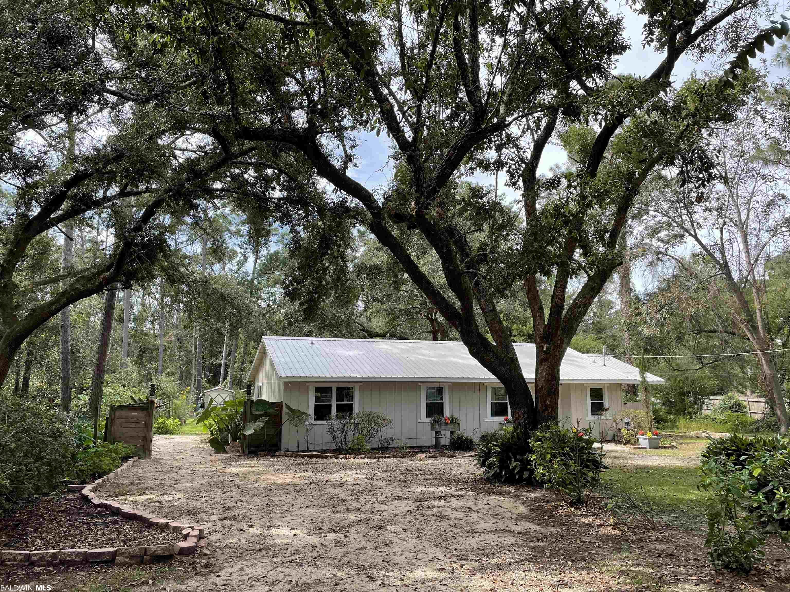 Beautiful home on a spacious lot near fish river.  Boat slip access.  Large wooded lot with outside area for entertaining.  Option to dig into canal on back of lot to make your own boat access.  This home is Price to Sell! There is a small access point already existing in the canal in the neighborhood that allows access to the water to get a boat in to lead to Fish River which leads Weeks Bay which leads to Mobile Bay/gulf. It's just past the house going towards the houses on the water but before them. Seller was told that the dry ditch/canal in the backyard could be dug out to create a passageway to main water. There are 3-4 satsuma orange trees that bear enough for daily fresh juice. Apple trees that just began to bear fruit last season. Fig tree that is fruit bearing. Several other fruit trees that include peach, pear and plum that should bear fruit next season. Many beautiful blooming mature hydrangeas, gardenias, azaleas, roses, to create fresh bouquets to decorate your home. Fire spike bushes and weeping camellias create dramatic foliage showing off nature's beauty. A majestic, live oak in the backyard provides comfortable shade. A walking path was created in the front yard with iron plants to lead you to your collection of mail from the from that mailbox. The roof and decking will be professionally cleaned as soon as the weather permits. This home is less than a 20 minute drive to the beach.
