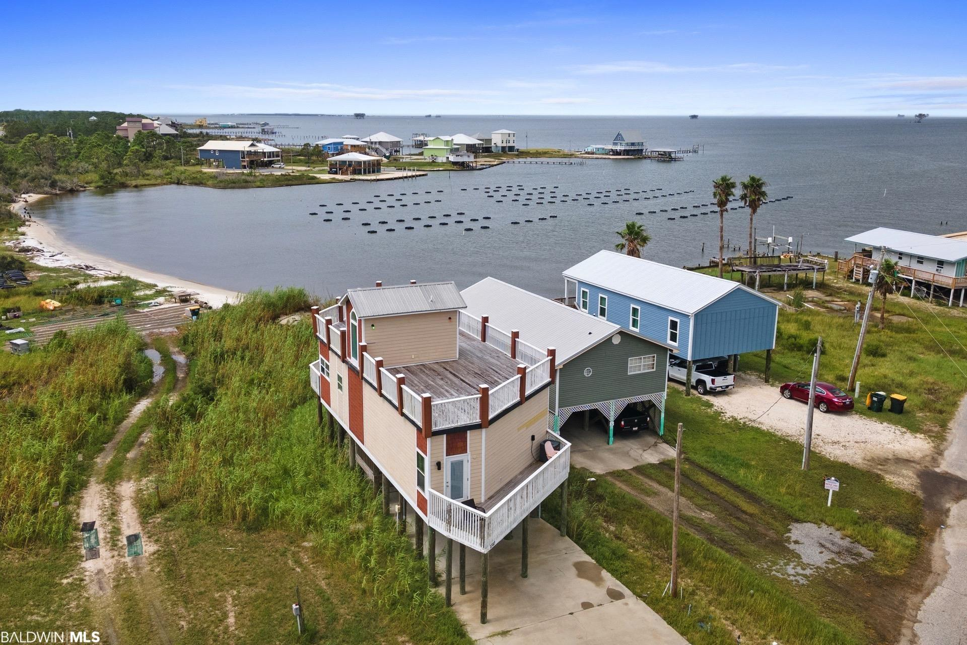 Fantastic beach house with views in every direction! Bay is right out back and the beach is a short walk. Engineered Plans attached to listing to add another floor and bedrooms. The house was Built from the ground up with that option in mind! Additional possibilities on rooftop deck are an outdoor kitchen!  Its also a great place to grow oysters in the Bay, See navy Cove oyster farm in the photos of the bay! Almost 5 stars in 52 rental reviews! When you walk into this beautiful home the first thing you notice is the amazing views! When you bring yourself to look at something other than the the views of water all around the house you will notice the granite counter tops, and tile throughout. Prefer to come in off the beach and not get all spruced up for dinner? No worries. There is fully equipped kitchen for just that. Also featured in this home is a dining area for 6, a full sized washer and dryer, Analog TV, and two full bathrooms. Best of all, this 2 bedroom home sleeps 5. Whether you are a family or a group of friends, you can all stay together without crowding one another. The home has 2 Queen beds and 2 twin rollaway beds. Other property amenities include Wireless internet, and direct access to the beach. Panoramic views of the Gulf of Mexico and Mobile Bay can be seen from your home! The Mobile Bay Ferry, Historic Fort Morgan, and a Marina are just minutes away, for all your boating/fishing/kayaking/exploring needs.