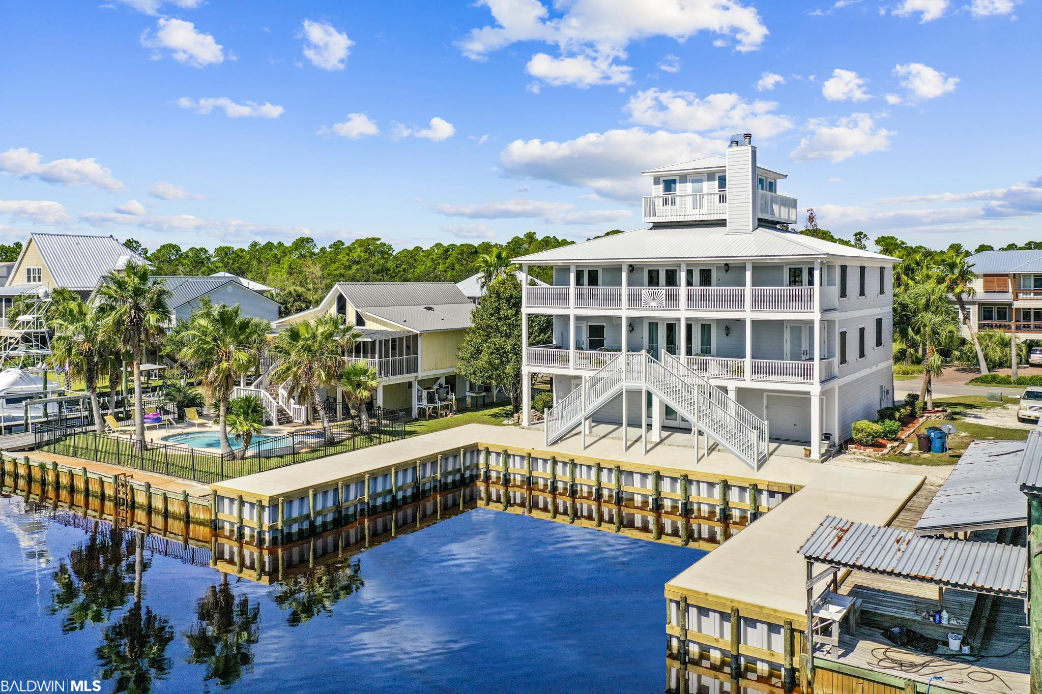 Conveniently located in the heart of Orange Beach, this beautiful home is perfectly situated on a wide canal leading to Orange Beach Marina, Fisher's, and Terry Cove. With seven bedrooms and over 8,500 total square feet under roof, the house offers a seemingly endless amount of space to live, entertain, and relax. This single-owner home has never been offered for sale and features nine-foot ceilings, crown molding, wood floors, two fireplaces, a whole-house sound system, plantation shutters, a plethora of windows allowing for an abundance of natural light, two kitchens, a massive entertainment room measuring over 1,400 SF, and a fourth story crow's nest offering panoramic views of Orange Beach. The fully remodeled kitchen boasts light-colored quartz countertops, a quartz backsplash, wood-block island, bar with seating for four, stainless steel appliances, and a built-in cooktop microwave, and oven. The spacious master suite features direct balcony access, a fireplace, large walk-in shower, separate jetted tub, double vanity, private water closet, and a large walk-in closet. The house is anchored by two heated and cooled attached garages that measure 40 feet in depth and total 1,080 SF. The exterior of the home is outfitted with Hardie-Board siding, a metal roof, impact resistant tri-latching doors, functional storm shutters, Trex decking, fiberglass encased handrails and columns, and over 2,000 SF of covered porches featuring bead board ceilings. The massive boat slip measuring 40' wide and 41' deep offers an endless amount of protected water and is outfitted with brand new pilings, seawall, and poured concrete dock. The time is now – come see this one-of-a-kind home before it is gone! *Please note that the stairs depicted in the rear of the house are not the actual stairs that exist. The stairs were being rebuilt at the time photos were taken.