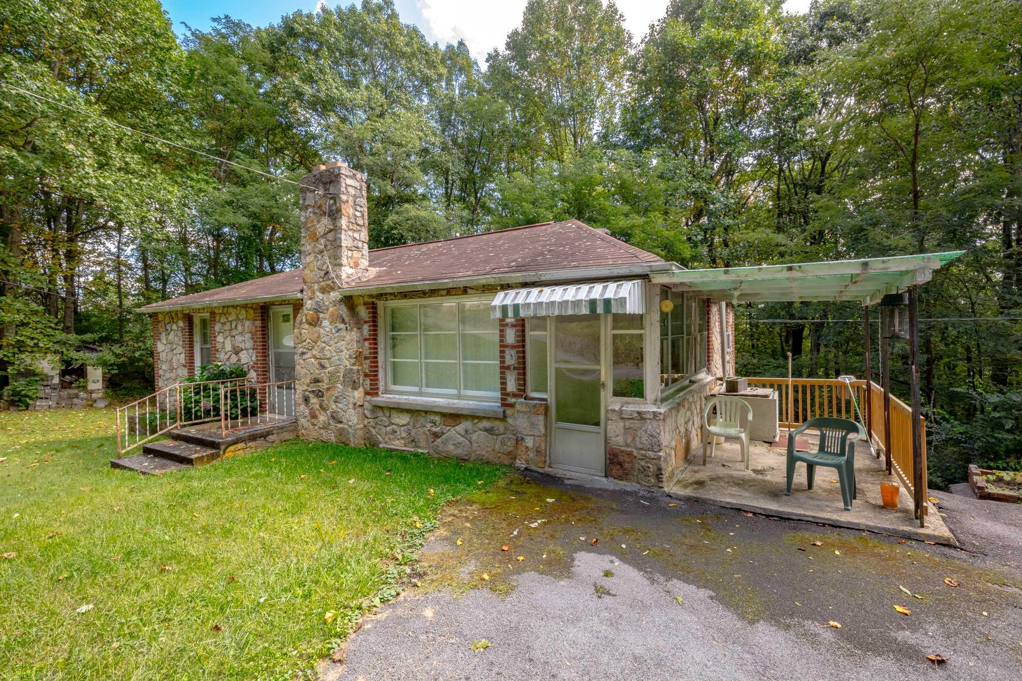 2 BR 2 BA home on +/-2.6 acres in the mountains of Southwest VA. This home has the mountain cabin retreat feel and provides a view in the fall and winter from E. River Mtn. Recent survey on file. Also includes an approx. 20x20 cinderblock garage ideal for yard equipment, etc. and a large frame garage big enough to most likely handle two vehicles, or simply use it as storage. Other features include a paved driveway, wood stove, wood burning fireplace, large living area, oil furnace heat, window unit for cooling, and more.