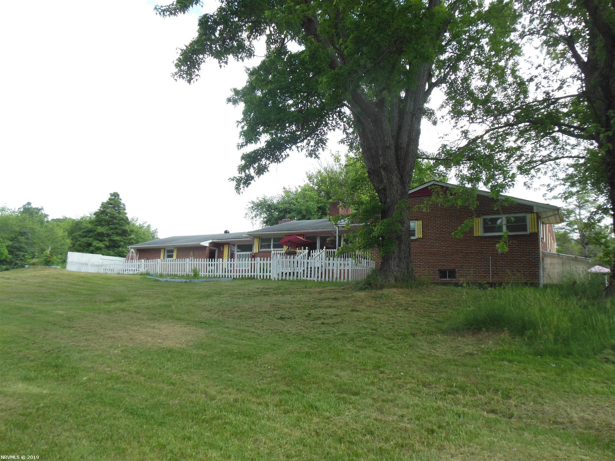 This renovated Brick rancher is huge with large formal and informal areas to live your life fully. The main house has 3-5 BRs and 2.5 baths sits on over 4 acres with additional mostly wooded acreage behind the barn/workshop. Property has 540 feet road frontage, picketed fenced front yard and fenced  yard for the kids, horses & other 4 legged friends. 10 minutes from Radford, this can be the mini farm you were dreaming about. Heat Pump for main level and Wood stove in lower level. Two kitchens and double attached garage and tons of character. The separate large barn with attached very large workshop is wonderful space for all animals you may have and mechanical/wood work shop you may need.