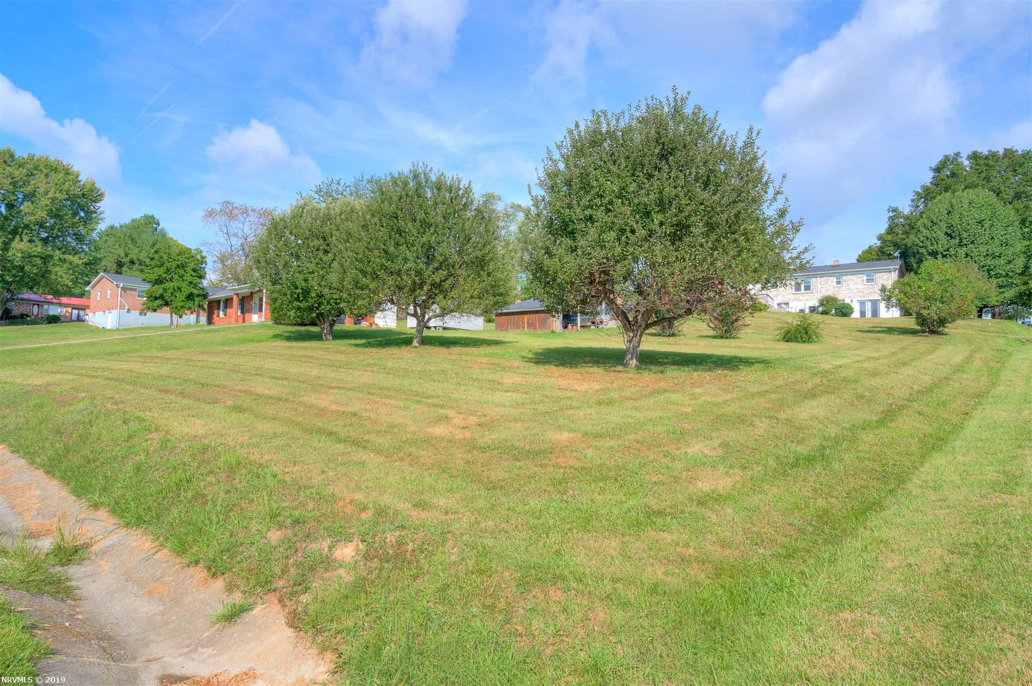 Very nice corner lot awaits your new home with several mature trees, Also there is a building with attached tractor shed on site, with newer roof and wired for electricity.