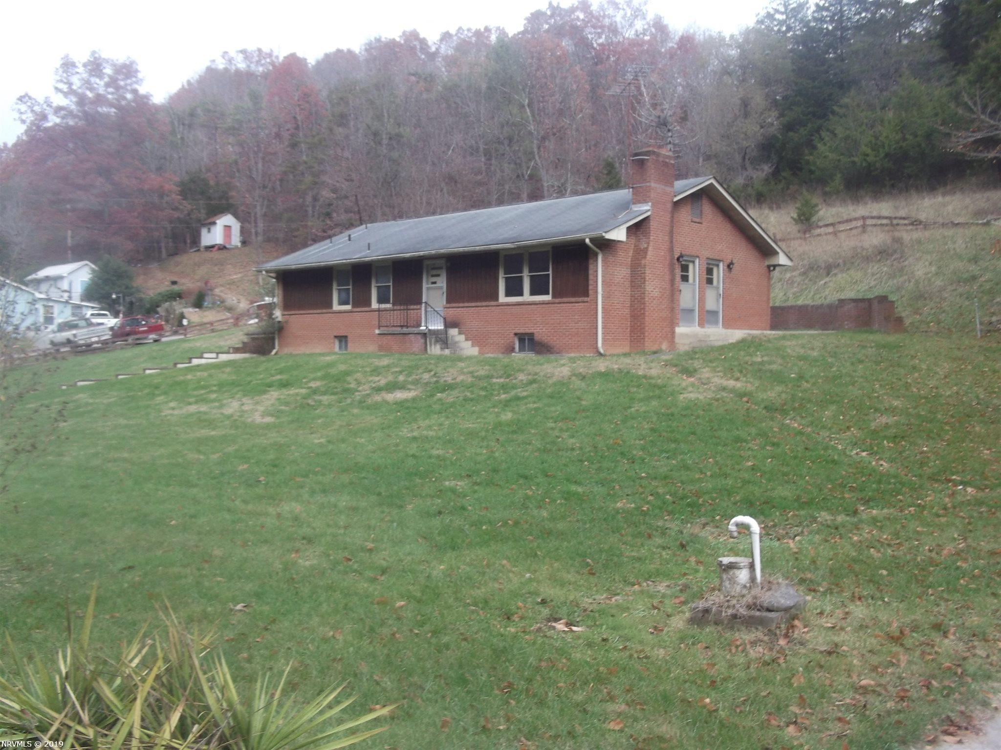 Affordable brick home on 2 acres.  Large living room with masonry fireplace.  The house interior has the original colors and paneling from when it was built but the home has been well cared for.  It is in Move in Condition. The large yard has a detached garage and a small stream across the front.