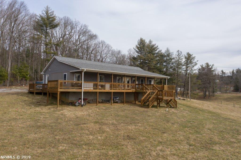 Bring your toys, cars, livestock, pets and your family to this unique hobby farm in Floyd County, Virginia. The incredibly well built, 2014 custom country home, features an open concept floor plan with 3 bedrooms & 2 full baths. The modern exterior with enormous wraparound porch still houses a cabin feel with the log and wooden interior. Modern touches include keyless entry doors throughout, tilt-in windows, french doors, antique hickory cabinets, butcher block counter tops, stainless steel appliances, tile flooring, brushed nickle hardware, & dual rainfall shower heads. Artesian well, climate controlled crawlspace, outdoor Hardy wood/coal stove, & foam insulation as thick as the walls keep your utility bills low! A true mechanic's garage featuring a 2 post lift and custom shelving, is any car person's dream. 3 separate, wide open & rolling pastures with water in each. A babbling creeks feeds a wildlife duck pond and larger 1/4 acre pond stocked with catfish. New fencing throughout.