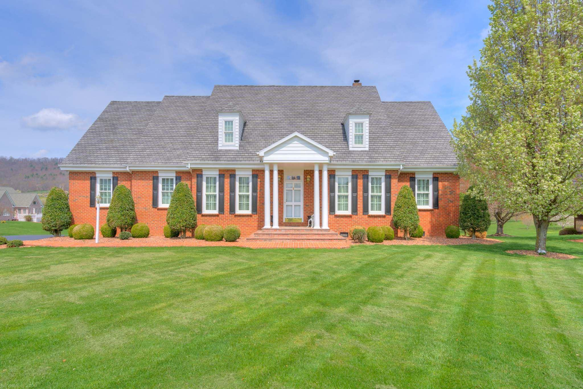 Stately all brick colonial impeccably maintained is picture perfect. A columned front porch and manicured landscaping welcomes you into a beautifully appointed home with decorative moldings, hardwood floors and big window views throughout. French doors open into the formal dining room with plantation shutters, and a crystal chandelier. The casual living room with a gas fireplace, built-in bookcases, recessed lighting offers mountain and golf course views!Gorgeous chef inspired kitchen offers an abundance of cherry cabinets, granite counters, breakfast bar, desk area, plus a dining area with views. Large laundry room with lots of cabinets, sink and folding space. Beautiful master suite has a private bath, soaking tub, separate shower, and dual sinks. Two additional spacious bedrooms with private baths complete the main level. Upper level bedroom with private bath, family room and den is ideal for guest or second living space. Come on over and enjoy the views from the cover brick patio.