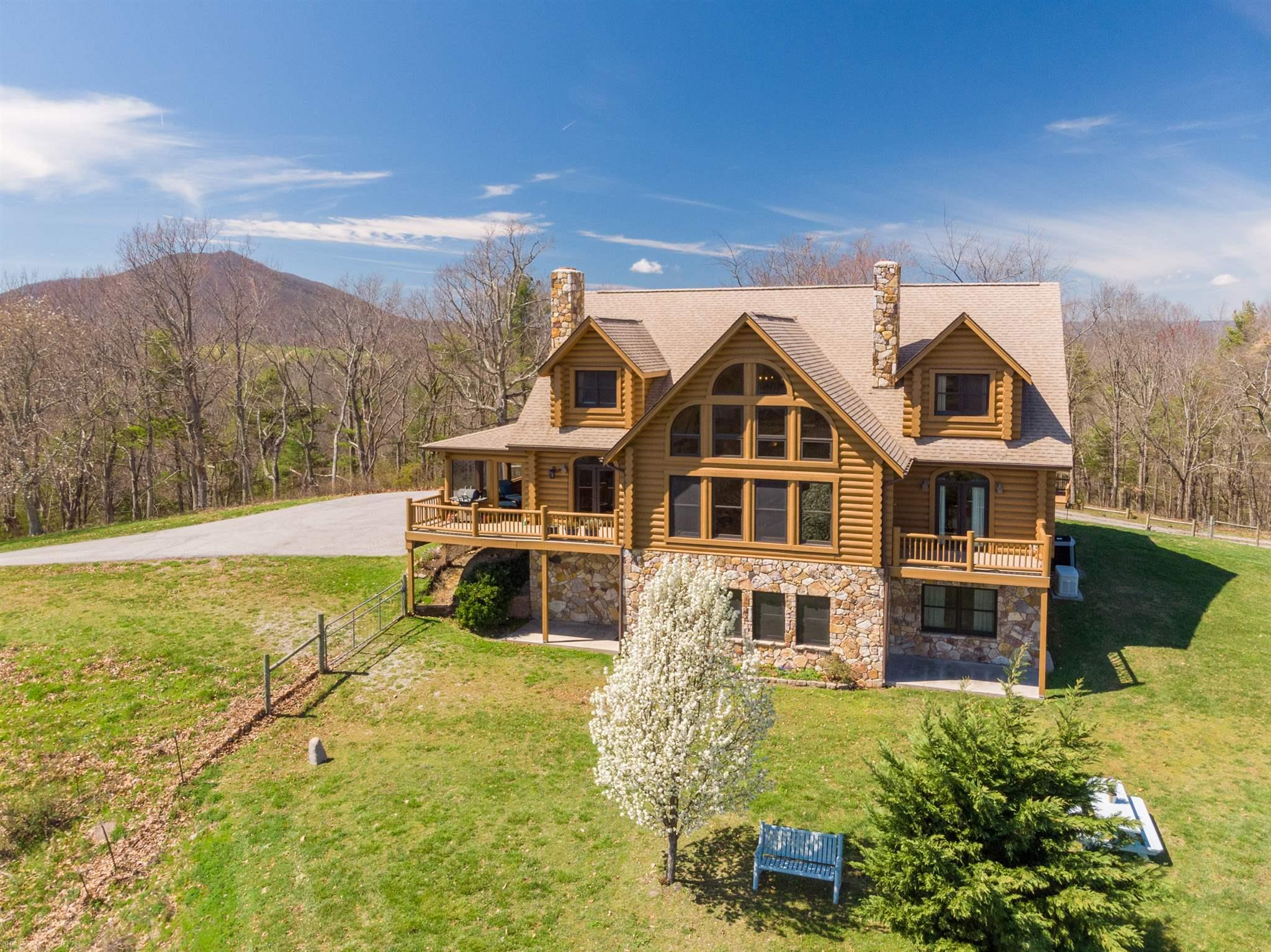 This stunning custom built 5 bedroom 4 1/2 bath log home situated on 65 acres is an outdoor enthusiast's dream come true! Enjoy magnificent 360 degree views of the beautiful Blue Ridge Mountains while you escape to the peace and quiet and rustic elegance this exquisite home offers. The gourmet kitchen boasts custom cabinets, Viking appliances, gas range, impeccable granite countertops, and enormous walk-in pantry.  The master bedroom is an owner's sanctuary & features a spacious en-suite bath with spa shower & tub, large walk-in closet, separate sitting room, and its own fireplace. Sit back & relax with a good book in the main floor library while sitting next to a roaring fire or watch your favorite movie in your own private theater room. Enjoy stunning views with your morning coffee from your own private deck, your favorite hobby in the huge detached double garage, an evening hiking down to the creek or to the two-stall barn to check on the resident alpacas. Showings by appointment.