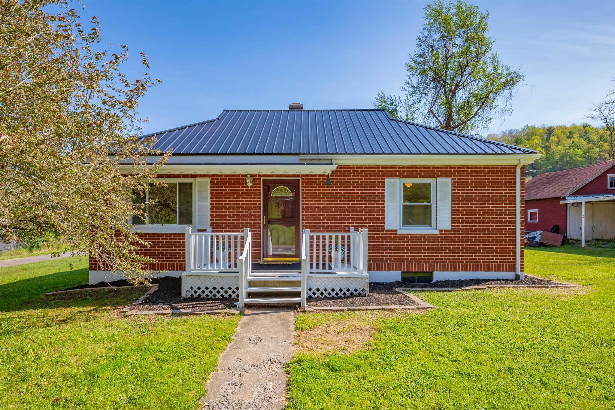 Charming 2 BR 1 BA brick home in Rocky Gap, VA on a nice, level lot that has been partially remodeled. Included is a large 2 car detached garage and a smaller outbuilding. Located literally within walking distance of Bland County High School and the post office. Features include a brand new metal roof, some new plumbing, heat pump for heating and cooling, mostly hardwood flooring, fresh paint, insulated tilt windows, public water, and it's own septic. Basement is unfinished. Nice large deck at the rear. Road frontage on state maintained road. Range/oven and refrigerator included as well. Terrific starter home for a younger couple or ideal for an older couple looking to downsize.