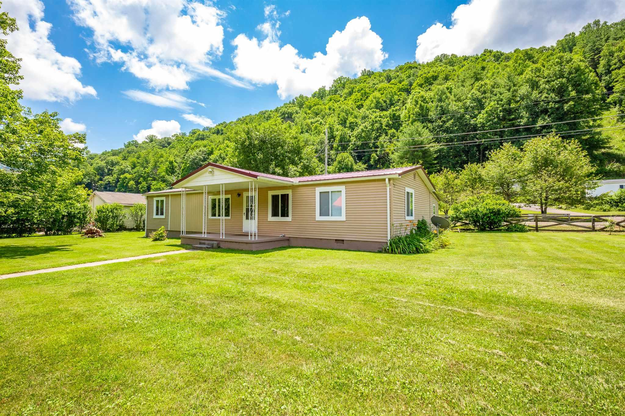 3BR 2 BA Doublewide on a permanent foundation in Rocky Gap, VA. This mostly remodeled home sits on 2 level lots with a commercial size garage (220 elec.), small storage building, and a larger storage building with a root cellar. Paved driveway with a triple carport, and LOTS of upgrades. New metal roof approx. 2 yrs old, new gutters, new deck, some fresh paint, new French doors, new front door, new picture window, some new interior doors, and all remodeled rooms were upgraded with sheetrock. Heat pump/central air, and a new fireplace with gas log insert. This is a must see and overlooks Wolf Creek. Includes apple, pear, and cherry trees, in a quiet neighborhood, extra parking, just 1 mile off of I-77 and approx. 13 miles to Princeton or Bluefield. Conventional financing or cash only.