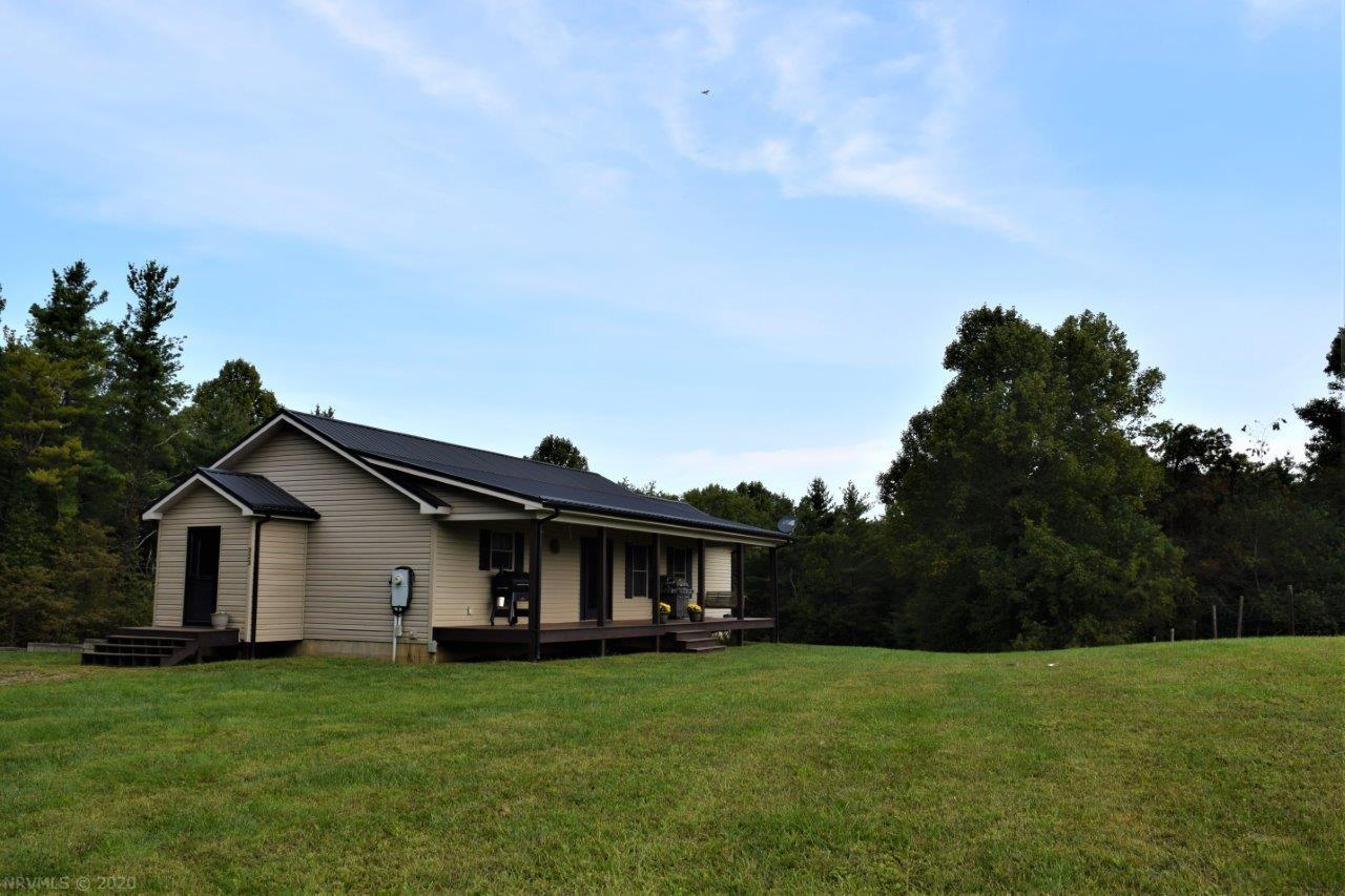 This beautiful home is settled in a peaceful country atmosphere while only minutes from the Town of Floyd and the Blue Ridge Parkway.  This property is wooded with gorgeous open pastureland which can be viewed from the privacy of the covered front deck.  The home is well maintained with a finished lower level.  The primary bedroom and bath are on the main level as well as the laundry.  The home office or reading room has an abundance of natural light making it the perfect room to sit and relax.  This home is perfect for those interested in a country setting with ample pastureland for a hobby farm.  The home has hickory wood floors throughout and is equipped with an outdoor woodstove to provide warmth for the cold winter days and nights.  Do not pass on this property, tranquility awaits!