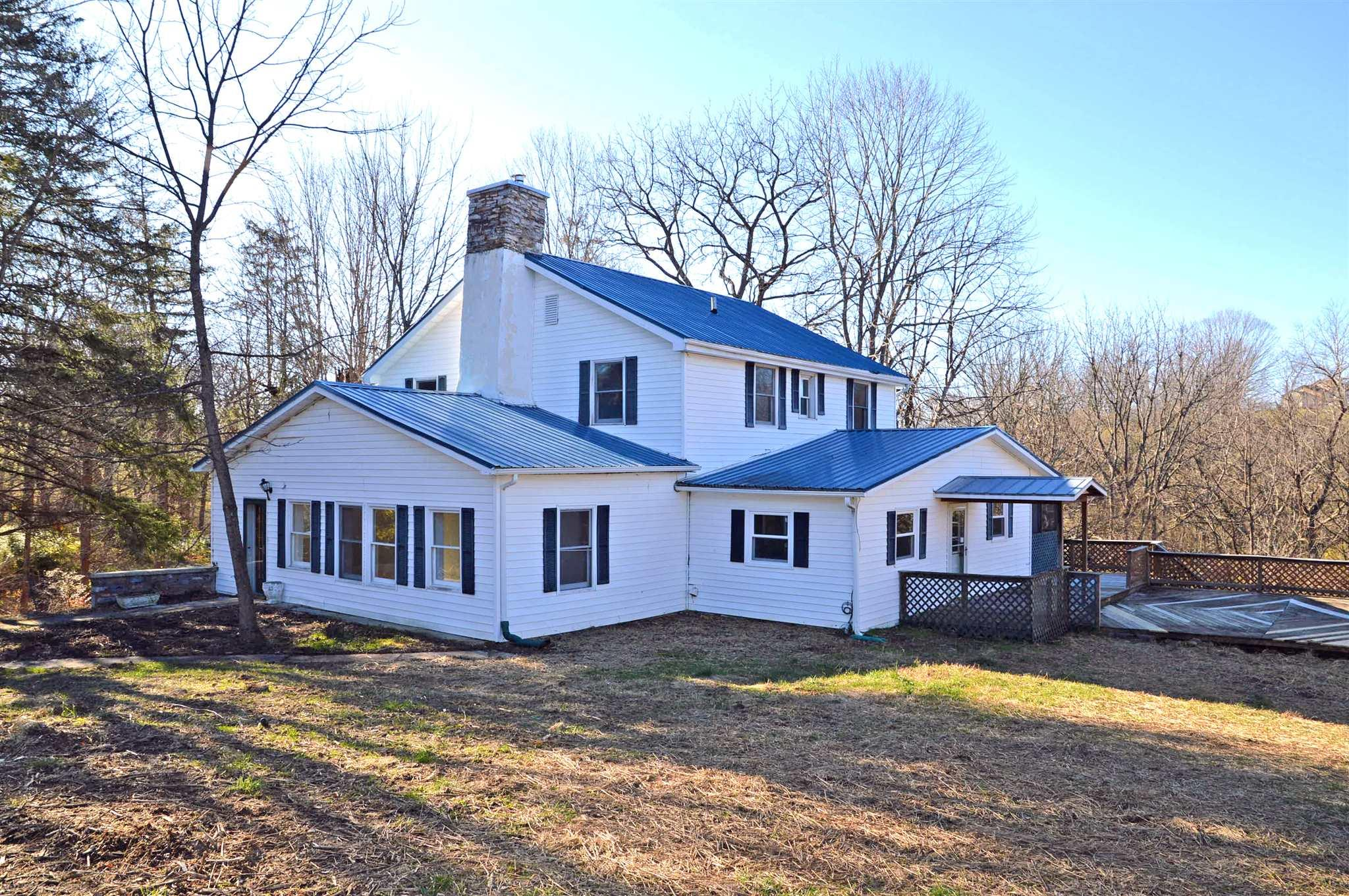 Check out the beautiful 5 acre setting for this 2685sf 4BR/2BA authentic farmhouse!  The fenced land is gorgeous and features a crystal clear twin springs with a stone springhouse, which feeds a bold brook that empties into Neck Creek which runs through the lower portion of the land.  The farmhouse offers large rooms and character at every turn.  Original hardwoods in almost every room.  The living room has a fireplace and built-in bookshelves. The huge main-level laundry room has a walk-in pantry. 3 bedrooms have cedar-lined walk-in closets. Some updates have been completed, most recently some fresh paint and new LVP floors in kitchen, breakfast room and laundry room.  A large screened porch and deck extend the living space outdoors.  A paved circular driveway is anchored by stacked stone columns.  Metal roof.  Call to tour today!