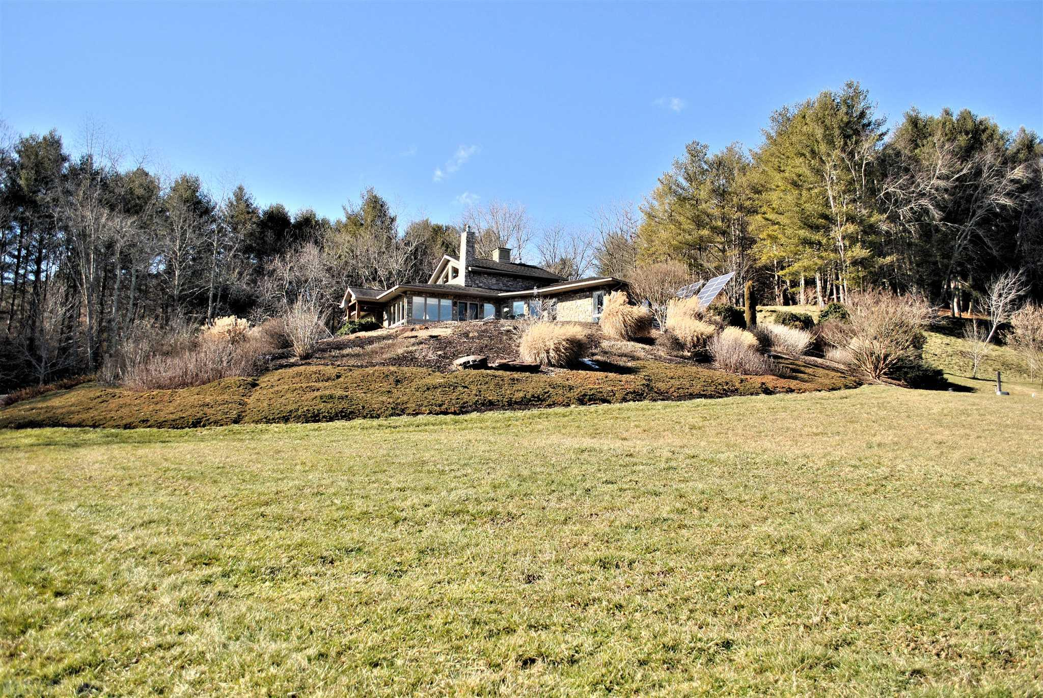 A magnificent, custom designed & built home overlooking Little River on almost 20 acres! Meticulous detail went into every inch of this masterpiece creating energy efficient living including radiant heat under beautiful concrete floors, solar panels, tankless water heater, zoned heating in four rooms, a SCAN  woodstove insert in the living room & a greenhouse! Soak in the sunshine & views of the river from the enormous patio, or through the many windows adorning the living room, dining room or master bedroom. There are many built-ins throughout including an entertainment center in the family room, a gorgeous bookcase in the hall, desks in two quaint offices & a large cabinet in laundry room as well as master bathroom. There is a luxurious, wood-fired  sauna in the second bathroom, root cellar & storage closet in the attached 2.5 car garage & a partially finished attic w/ pull down stairs for additional storage space. This home was lovingly built to last & is an absolute treasure!