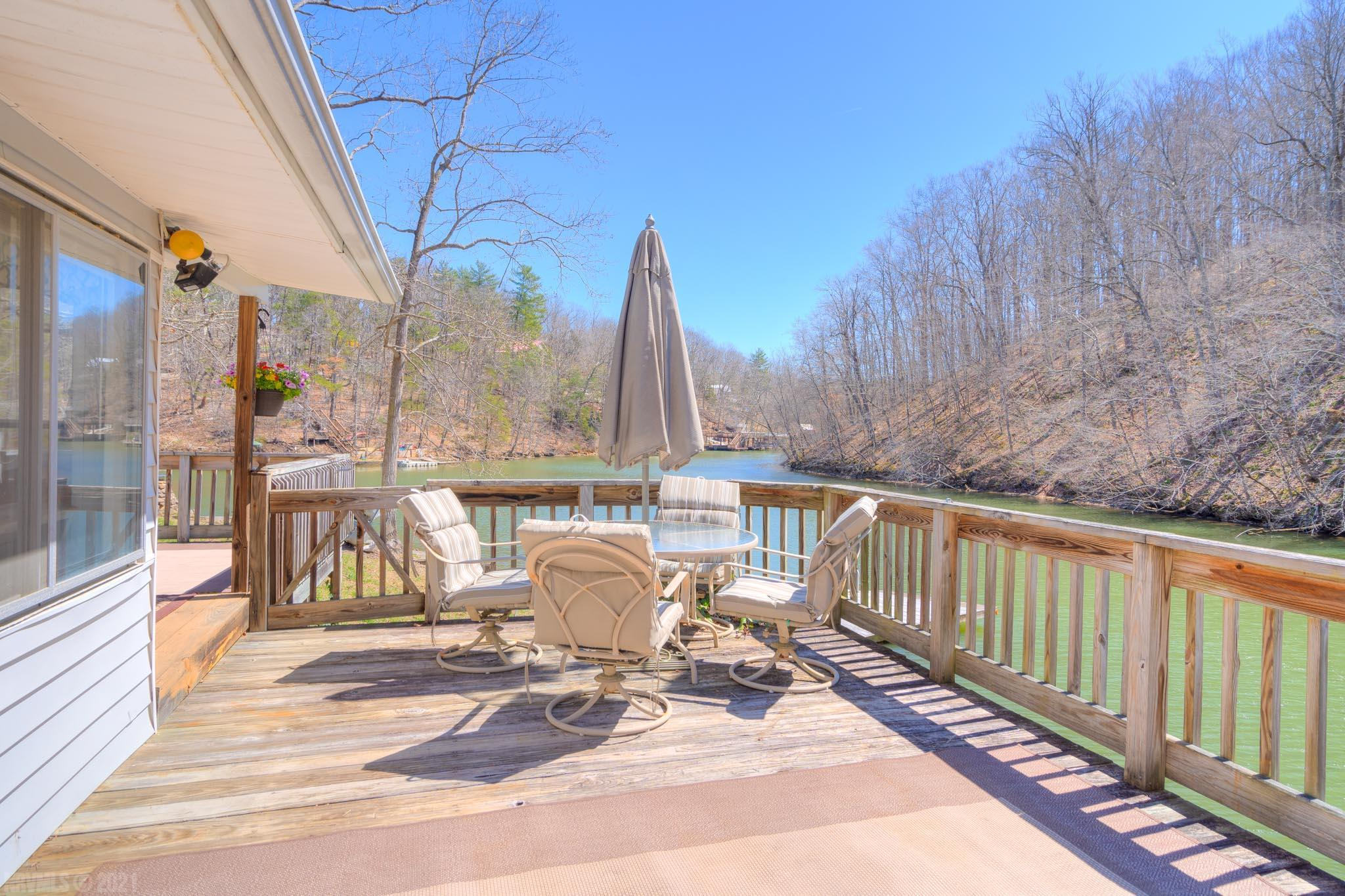 This home is a vacation lover's delight! Relaxing on your massive deck, enjoying Claytor Lake's water views and nature at its best, makes every day a vacation day! The living/dining room boosts a wall of windows bringing the outdoors in and maximizing the lakefront location. A light and bright kitchen offers lots of work and storage space and the bedrooms are nicely sized. The floating dock is the perfect spot for your boat with a 12' water depth near the dock and the private boardwalk is ideal for fishing. Beautiful 100 feet of secluded waterfront makes this an ultimate vacation home. Once you experience the tranquil water views you won't want to leave!