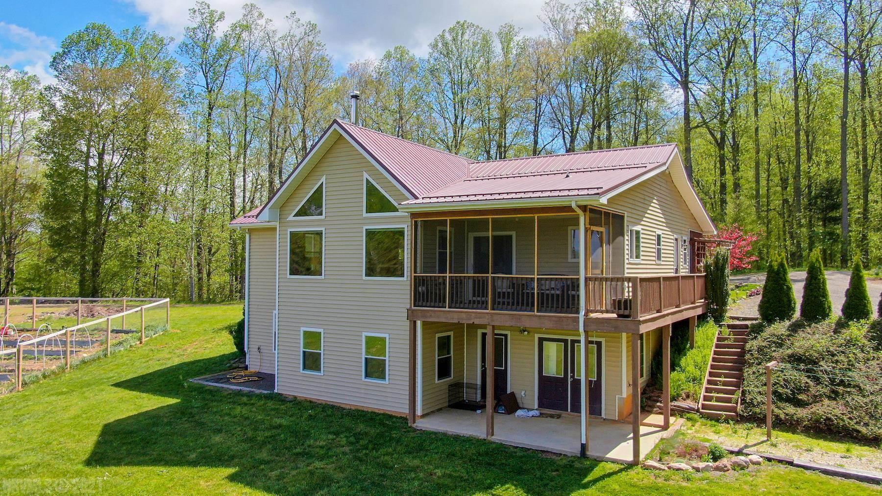 Incredible home with acreage in beautiful Floyd, VA! This property features a stunning 3200+ sqft. home with 5 bedrooms and 3 full baths. Several major updates since 2019 include a remodeled kitchen, updated bathrooms, flooring, and more. The home is perfectly situated on 16.73 acres to savor epic views of the Blue Ridge Mountains and complete privacy. Spend summer evenings enjoying sunsets and sweet mountain breezes on the screened-in deck. In the winter, stay warm with cozy radiant heated floors on both levels. There is a full finished basement with 3 bedrooms, 1 bath, another living room, and storage galore. There is wooded and open land, a newly fenced in garden, spring water, and fruit trees. There is an enormous 1400 sqft heated garage. The winding driveway brings you through the woods with babbling streams and age-old rock walls. Create the hobby farm of your dreams and enjoy country living at its best!