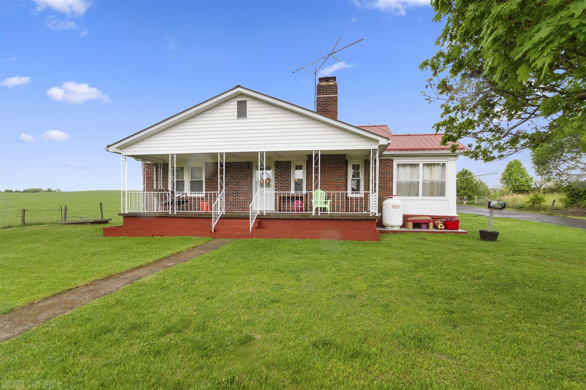 Charming brick ranch with 3.3 acres. Flowing floorplan features 2 bedroom and 2 full baths. (Additional bath/laundry area added in 2020). Living room with gas fireplace, formal dining room, floored attic with SO much storage space, mudroom and bonus sunroom. Metal roof, newer heat pump (2019) covered front porch, detached garage, partial basement and several outbuildings. Electrical box upgraded in 2019, interior painted over the last several years, exterior walls (sunroom) and basement painted 2021.