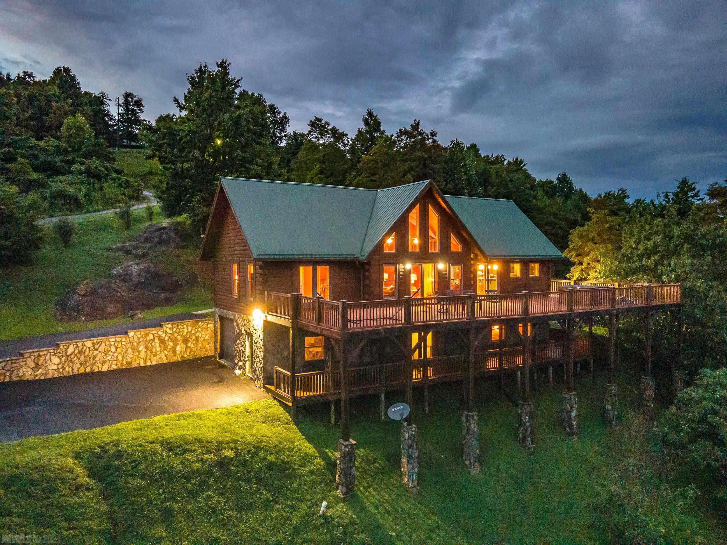 Are you looking for a log home with the best view of the Piedmont area in all of Fancy Gap? This spacious 5 bedroom cabin (including oversized loft) has a hillside design that provides expansive views throughout. Open floor plan offers living room w/gas fireplace and ceiling to floor windows with French doors leading to deck. The 70' x 22' composite top deck off the main floor provides for spacious entertaining and offers a new hot tub. Ample parking makes this home a great candidate for a vacation rental. Large laundry/mud room/pantry off of kitchen with separate entrance and separate driveway for easy access. Basement has large living room with a gas fireplace, a full bathroom and 2 bedrooms with its own 62 x 10 deck, and an attached garage. The home has a whole house generator as well. The home is located minutes off the Blue Ridge Parkway, and is at the edge of the subdivision. Come enjoy the abundance of serene nature and this spectacular view!