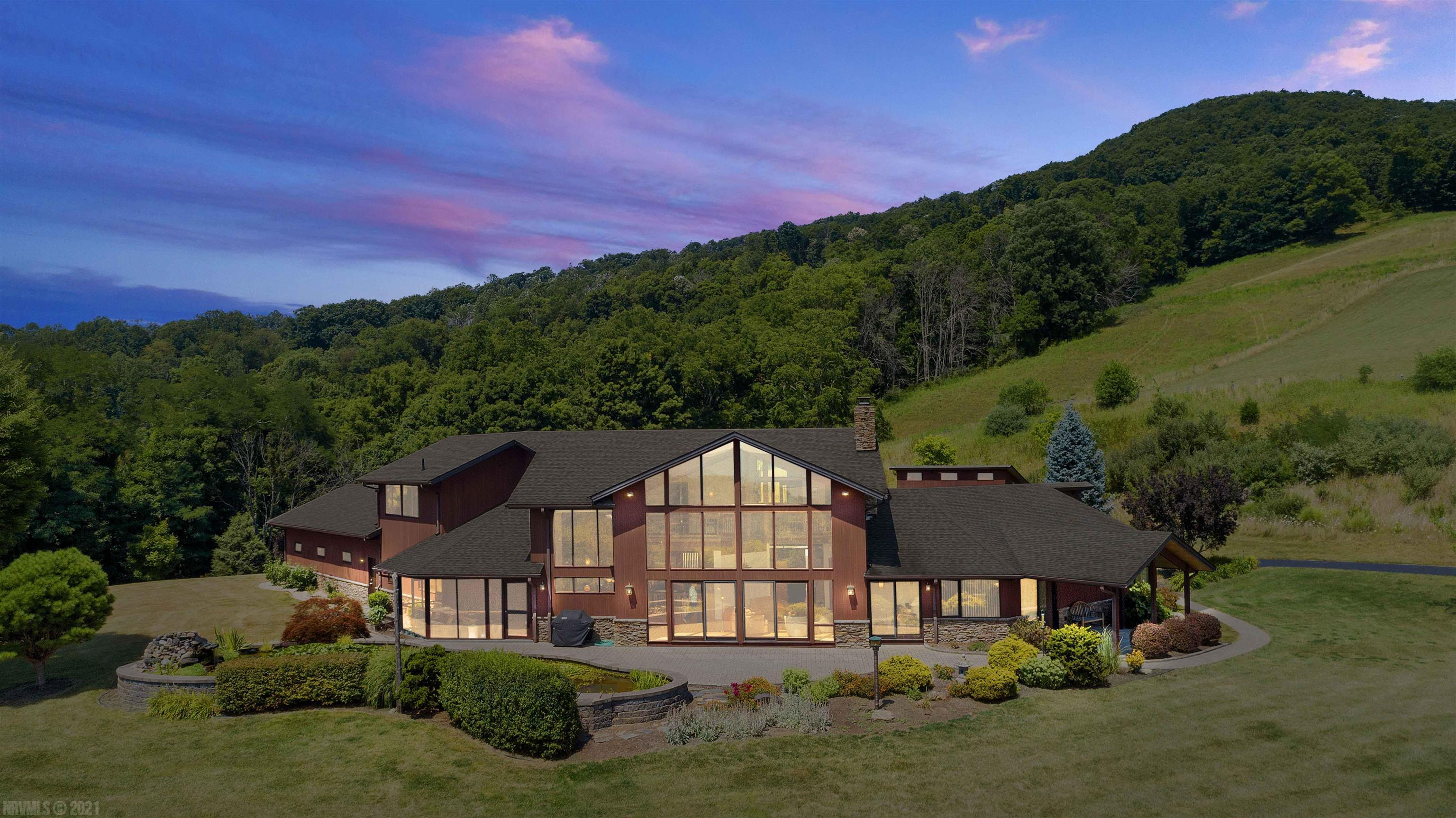This 5,151 sq. ft. open contemporary sitting in an open meadow just below Mtn. Lake Resort, 10 minutes from Blacksburg town limits is a resort in itself.  The 4 bd. rm., 3.5 bath home was meticulously built with attention to every detail beginning with the Western Red Cedar siding, exposed Douglas Fir Structural beams, solid Mahogany interior trim, geothermal HVAC system, two 80 gallon water heaters, custom cherry and oak cabinetry and ending with a 9,000 gallon custom water garden.  See the Custom Feature Sheet in documents section.  This home is extremely energy efficient, average electric bill over the last 3 years has been $188.00/month.  Privacy, PANORAMIC VIEWS, ease of access to locations like Lane Stadium, the Appalachian Trail and I-81 make this a must see location. There's also a 700 sq. ft. shop complete with water and electric.  A mountain spring fed stream runs along the northeastern boundary.  CLICK ON UNBRANDED MEDIA 1 & 2 ABOVE TO SEE DRONE VIDEO AND A VIRTUAL TOUR