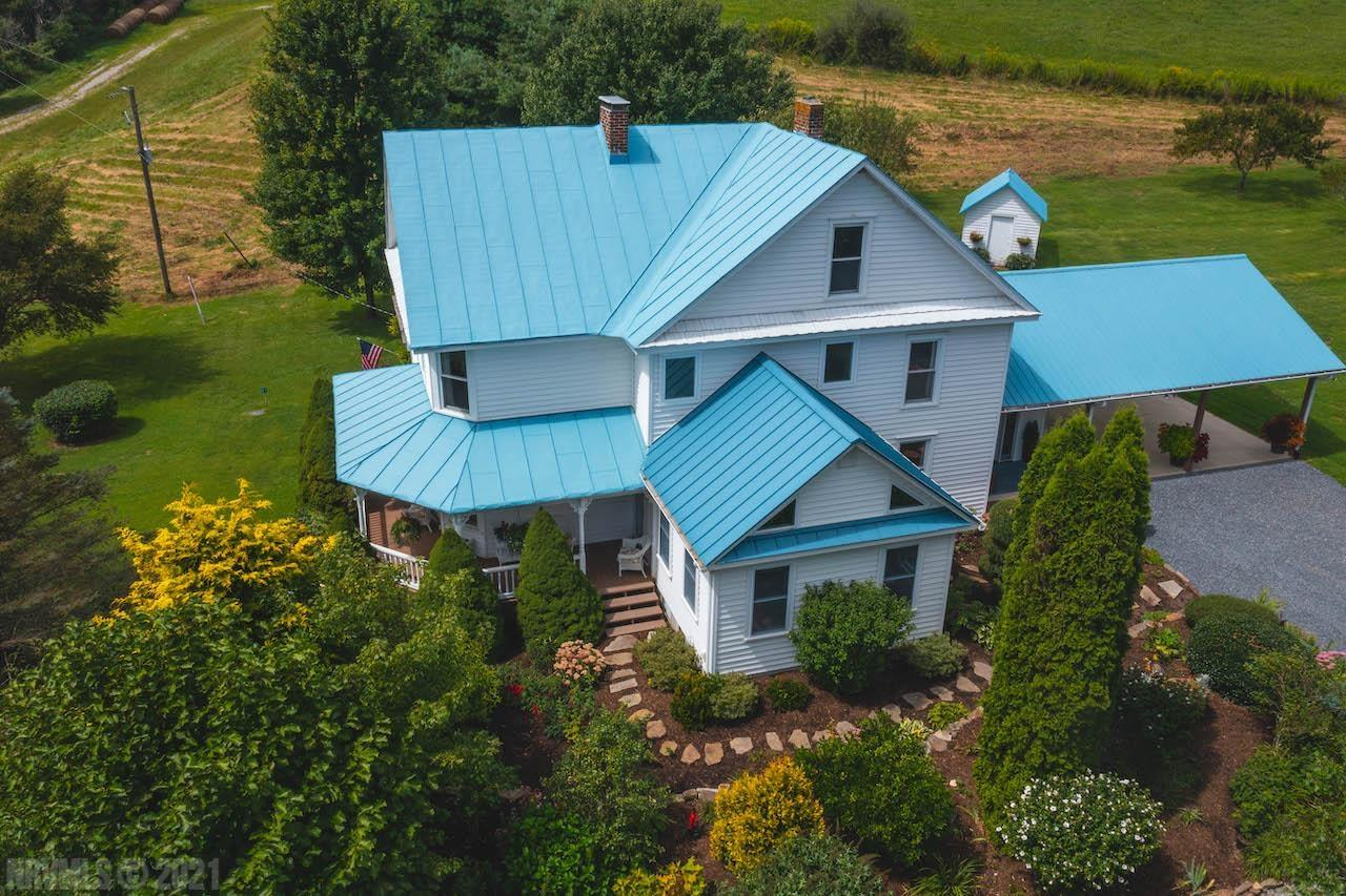 """Online Only Auction ending October 7th @ 4 PM! Price is starting bid, not reserve. Stunning Farmhouse for Sale in Floyd VA! This incredible home was built in 1902 but has undergone many updates to make it modern. Not only does the property feature a stunning home, it also consists of 39.89 acres with a nice mix of wooded and open land. There are several springs, 2 creeks, walking trails and an abundance of wildlife. The charming, well-maintained farmhouse has 2,510 sq. ft. with 3 bedrooms and 2 baths. The home has been professionally upgraded and enlarged to include plumbing, electric, foundation, windows, vinyl siding, reclaimed oak hardwood floors, living room addition as well as a large 33x23 carport with mudroom and pantry. The yard provides a large level area for endless play, stone fire pit, mature flower gardens with numerous perennials, outbuildings and woodshed. There is a large 42x20 """"Party Deck"""" with Pergola, as well as a nice covered front porch."""